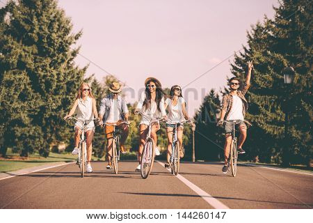 Enjoying nice summer day together. Group of young people riding bicycles along a road and looking happy