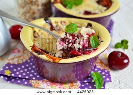 Cherry crumble with porridge on a concrete background