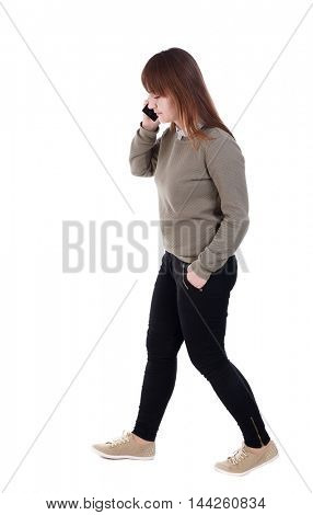 side view of a woman walking with a mobile phone. with his hand in the pocket of a girl talking on the phone