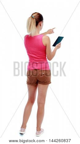 back view of pointing young beautiful woman and using a mobile phone. backside view of person. Isolated over white background. Sport blond in brown shorts reading an e-book and shows up finger.