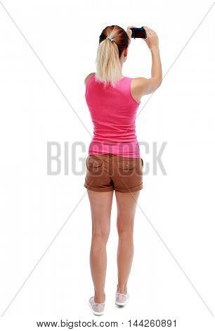 back view of standing young beautiful woman and using a mobile phone. Isolated over white background. Sport blond in brown shorts takes something in the sky.