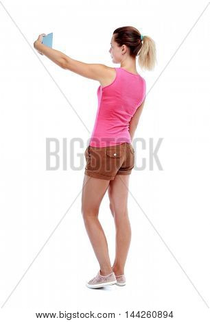 back view of standing young beautiful woman using a mobile phone. girl watching. Sport blond in brown shorts makes horizontal selfie on the tablet.