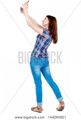 back view of standing young beautiful woman using a mobile phone. girl watching. Girl in plaid shirt standing sideways and photographs on your smartphone.