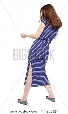 back view of standing girl pulling a rope from the top or cling to something. girl watching. Isolated over white background. The brunette in a blue striped dress stands sideways and pulling rope.