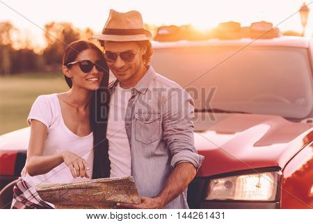 We should see this place. Beautiful young couple bonding to each other and leaning at their pick-up truck while examining map together
