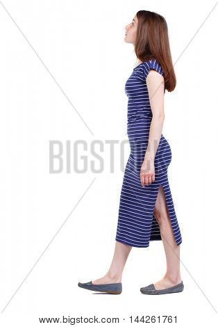 back view of walking woman. brunette in a blue striped dress goes to the side looking up.