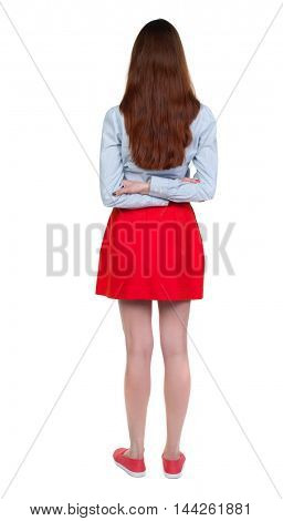 back view of standing young beautiful woman. Long-haired brunette in red skirt standing with his hands behind his back.