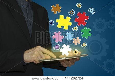 Businessman holding tablet shining puzzle pieces in his hand
