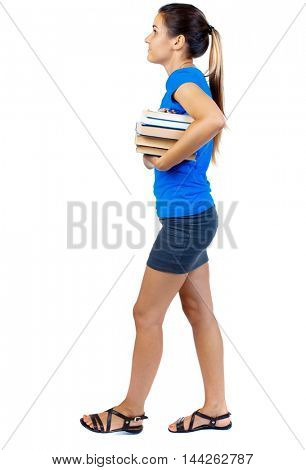 Girl comes with stack of books. side view. girl in a short skirt and a blue T-shirt goes to the side with books and looking ahead.