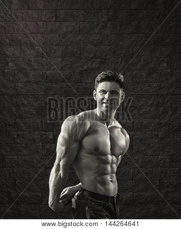 Young fit man is smiling and showing muscles -- monochrome stylized photo