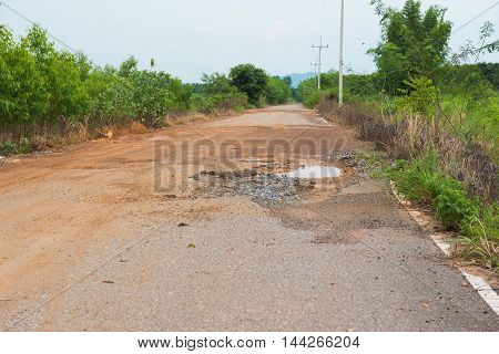 tarmac road in the countryside with potholes and puddles