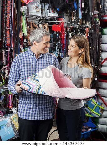 Couple Holding Slipper Shaped Pet Bed At Store