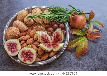 Plate with a variety of nuts and figs. Sprigs of rosemary and pomegranate. Still life. Concept - healthy food.