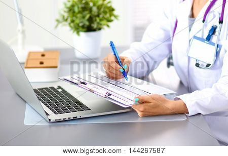 Portrait of young woman doctor in white coat at computer.