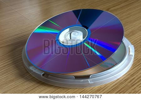 DVD disc for data storage on wooden table.