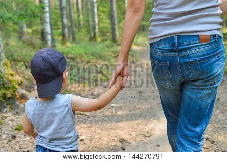 Cute little boy close-up walking in park holding parents hand. Happy family and lifestyle concept.
