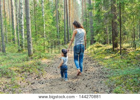 Cute little boy walking in park holding parents hand. Happy family and lifestyle concept.