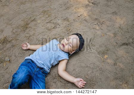 Little boy laying on ground pretending sleep or unconscious.