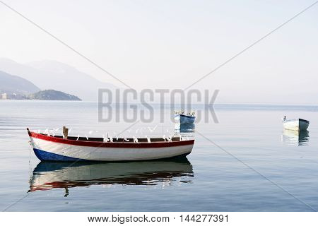 Fishing boats standing still on a beautiful lake in Ohrid Macedonia early in the morning with reflection on water