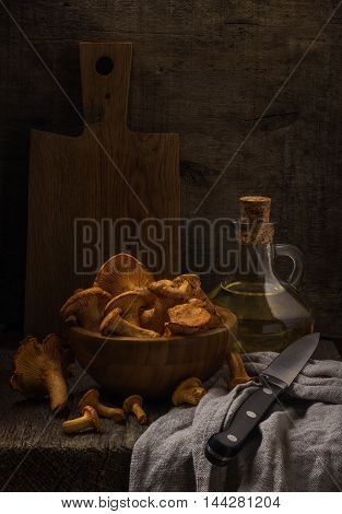 Classic rustic still life with chanterelles on the rough wooden background