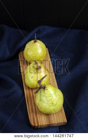 Still life with pears on wooden desk against deep blue table cloth. Low key.