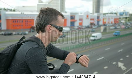 Outdoor portrait of modern young man with smart watch in the street. The man in glasses with backpack sitting on the bridge. Bottom drive cars.