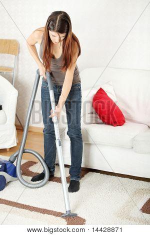 Hausarbeit, junge schöne Frau mit Staubsauger zu Hause. Hausarbeit-Konzept