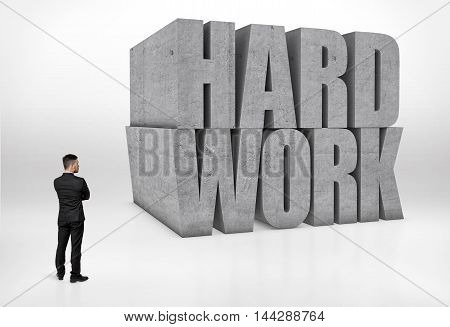 Back view of a businessman looking at big concrete 3D words 'hard work' isolated on white background. Dream big, work hard. Pondering and contemplating. Business staff.
