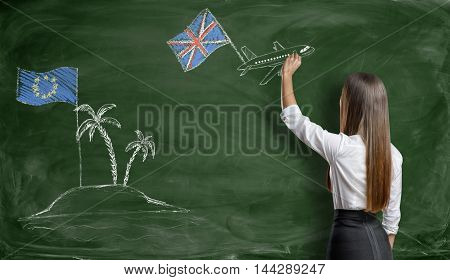 Businesswoman drawing a plane with british flag that flies away from an island with EU flag on blackboard. Brexit. British withdrawal. Euroscepticism.