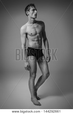 Model Tests. Handsome Man With Perfect Body Posing On Gray Background