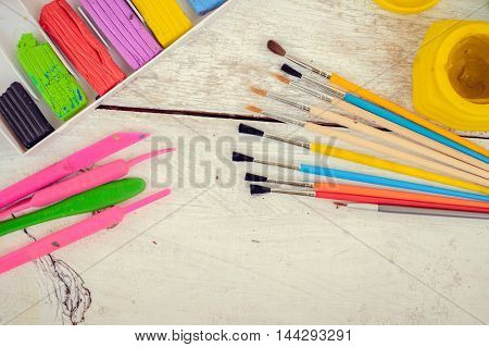 Tools for creative work on a white wooden background. Watercolor paintbox. Color paints with paint brushes and plastic