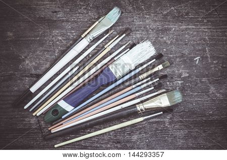 Paint brushes on a wooden background. Tools for creative work.