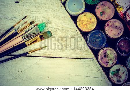 Artist paint brushes and gouache paint jars on white wooden background. Brush paint artistic. Tools for creative work.