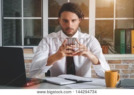 Handsome Young Businessman Sitting At His Workplace And Looking At His Smartphone. Business Theme