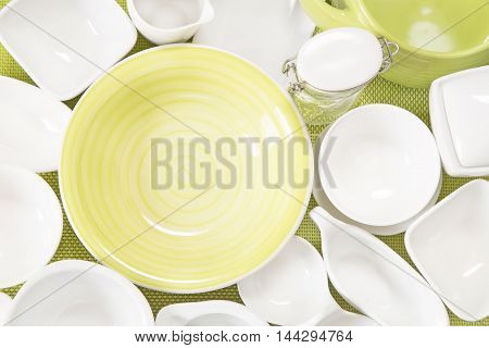 Various white porcelain dishes on green background
