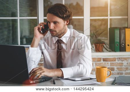 Handsome Young Businessman Sitting At His Workplace Looking At His Laptop And Talking At Smartphone. Business Theme