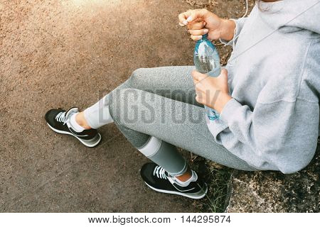 Woman in sportswear sitting in the park with a bottle of water and resting after a workout