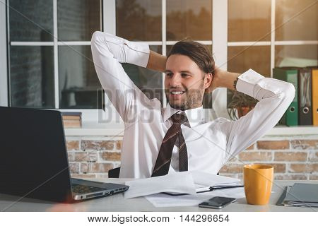 Handsome Young Businessman Sitting At His Workplace With Hands Behind Head And Looking At His Laptop. Business Theme