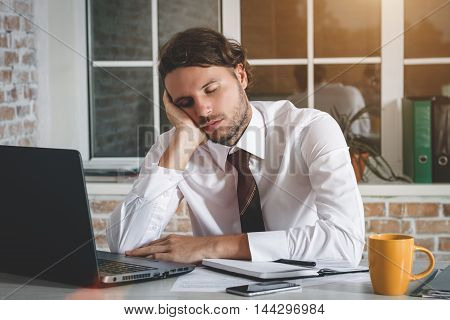 Sleeping Young Businessman Sitting At His Workplace. Business Theme