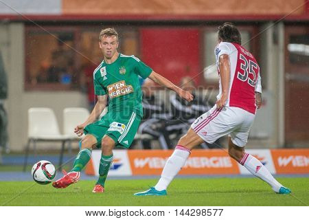 VIENNA, AUSTRIA - JULY 29, 2015: Philipp Schobesberger (SK Rapid) and Mitchell Dijks (Ajax) fight for the ball in an UEFA Champions League qualification game.