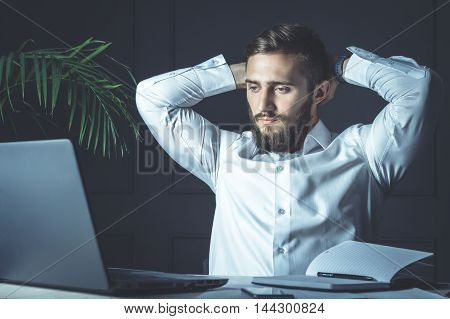 Handsome Young Bearded Businessman Sitting At His Workplace With Hands Behind Head And Looking At His Laptop. Business Theme