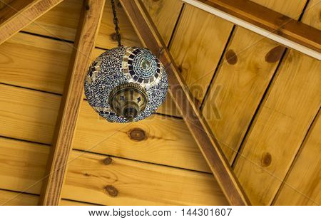 Decorative, Oriental style lamp against of the wooden ceiling. Stock photo