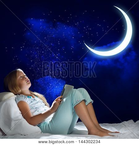 Girl sitting in bed and using her tablet pc