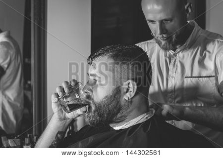 Serious Bearded Man Getting Haircut By Barber And Holding A Glass Of Whiskey While Sitting In Chair At Barbershop. Barbershop Theme