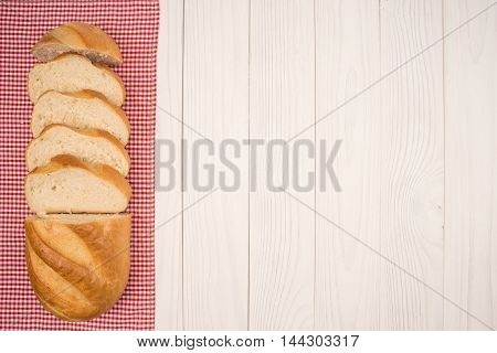 Loaf of bread on a wooden white table. Top view