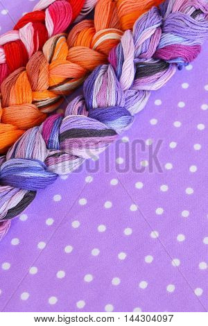 Embroidery threads of different colors on a purple background. Colored embroidery threads. Embroidery thread set