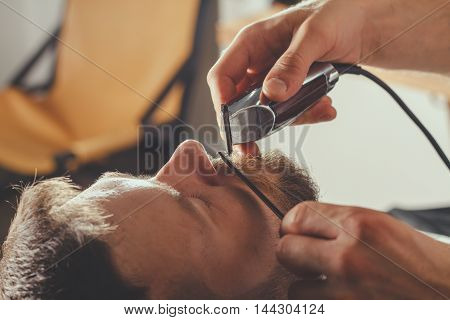 Serious Bearded Man Getting Beard Haircut By Barber While Sitting In Chair At Barbershop. Barbershop Theme