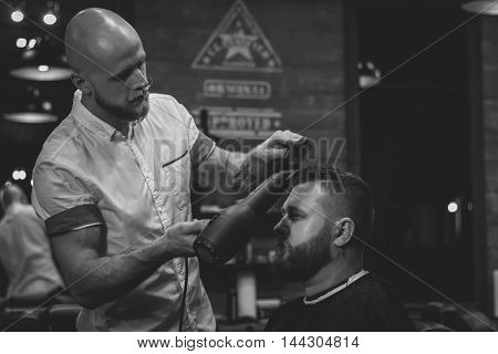 Serious Bearded Man Getting Haircut By Barber While Sitting In Chair At Barbershop. Barbershop Theme