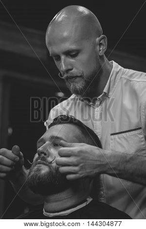 Serious Bearded Man Getting Mustache Haircut By Barber While Sitting In Chair At Barbershop. Barbershop Theme