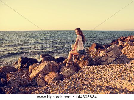 Beautiful Woman Sitting On The Rock Near The Blue Sea With Relaxing Look